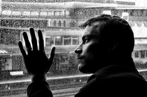 Mann schaut traurig aus dem Fenster